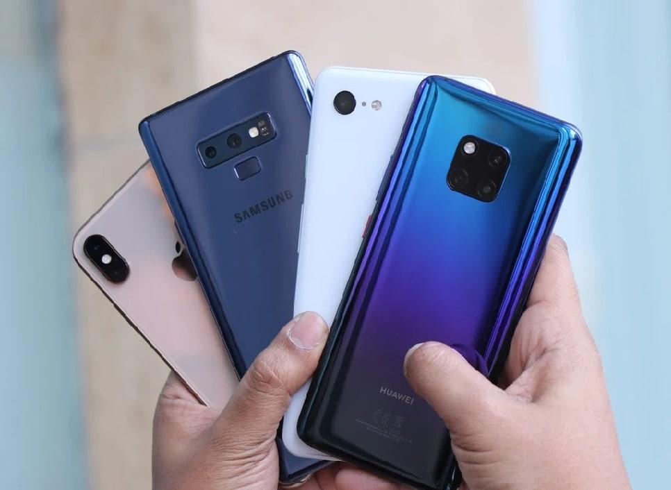 Hands holding 4 smartphones of different brands