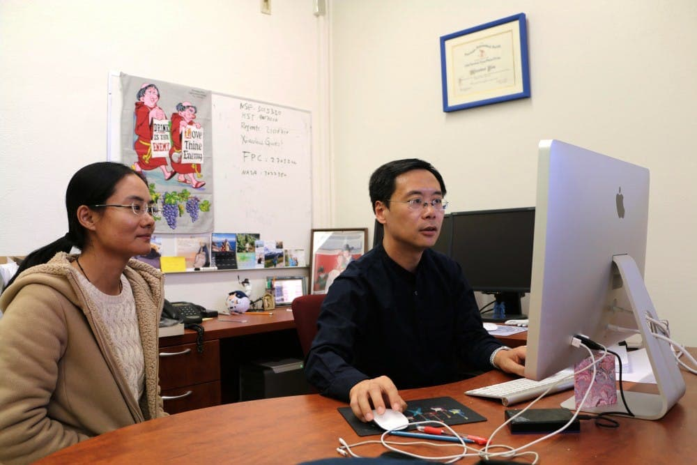 Xiaohui Fan, a regents' professor of astronomy at UA, and his post-doctoral researcher, Jinyi Yang, look over data collected from the Hubble Space Telescope of a black hole they discovered while observing the early universe.