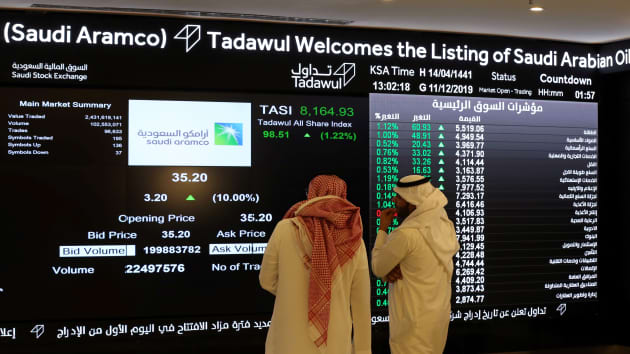 Investors monitor a screen displaying stock information at the Saudi Stock Exchange.